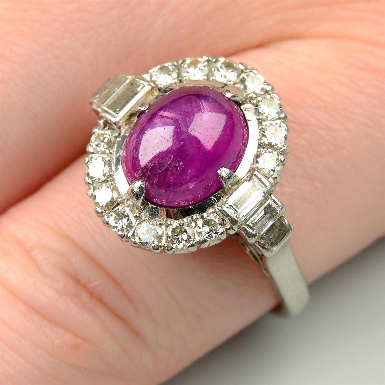 A ruby cabochon and vari-cut diamond cluster ring.