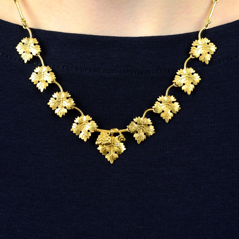 A diamond accent grape and vine leaf necklace, by M. Buccellati.