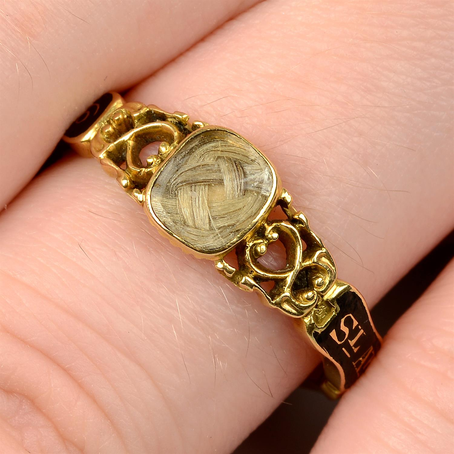 An early Victorian 18ct gold black enamel mourning ring, with pierced scrolling sides and woven