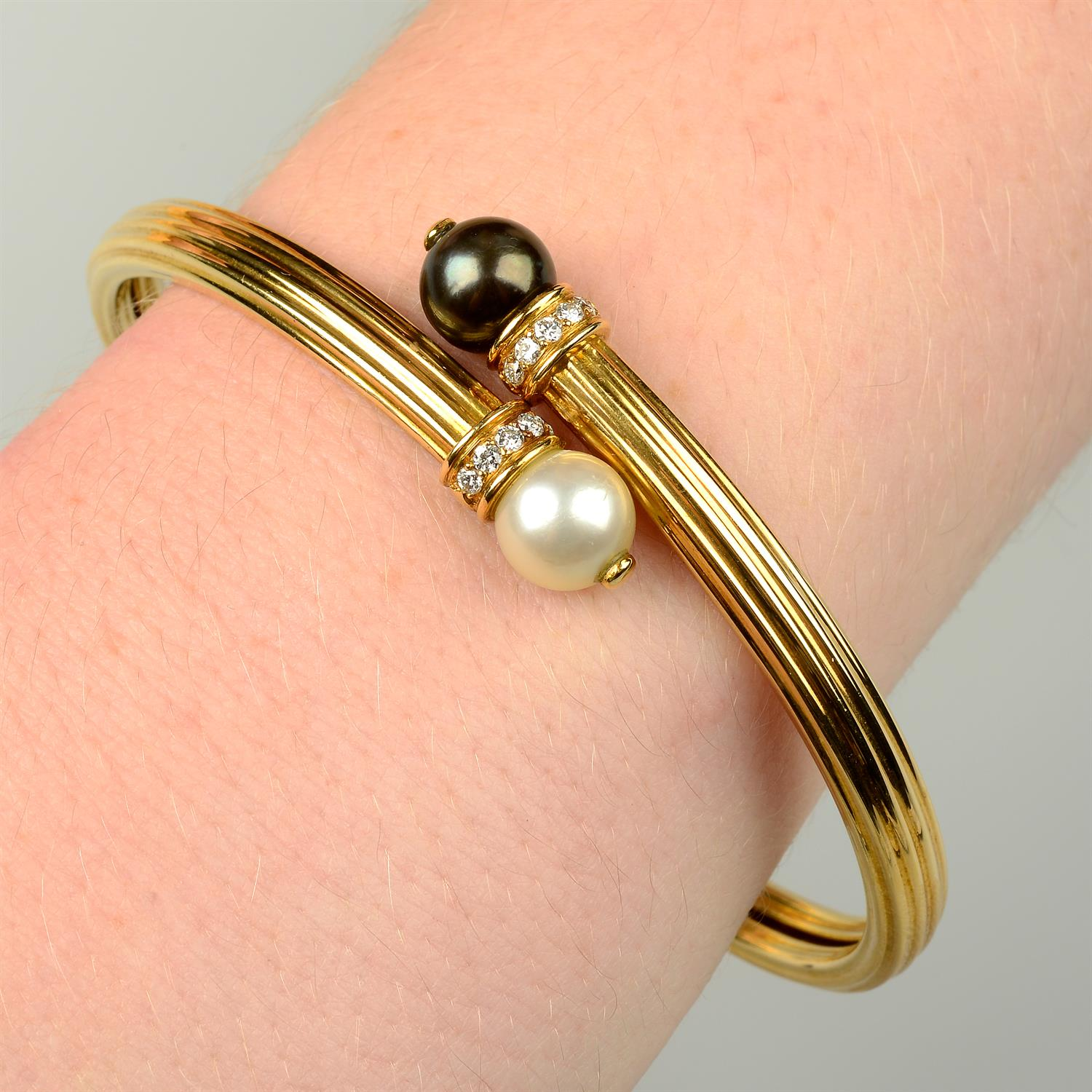 An 18ct gold grooved crossover bangle, with vari-hue cultured pearl and brilliant-cut diamond