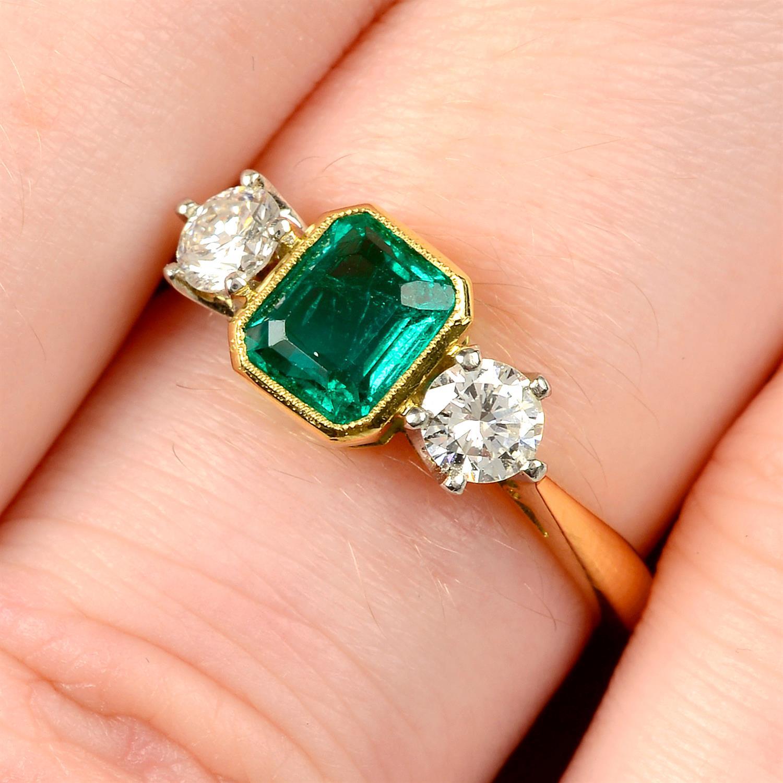 A platinum and 18ct gold emerald and brilliant-cut diamond three-stone ring.