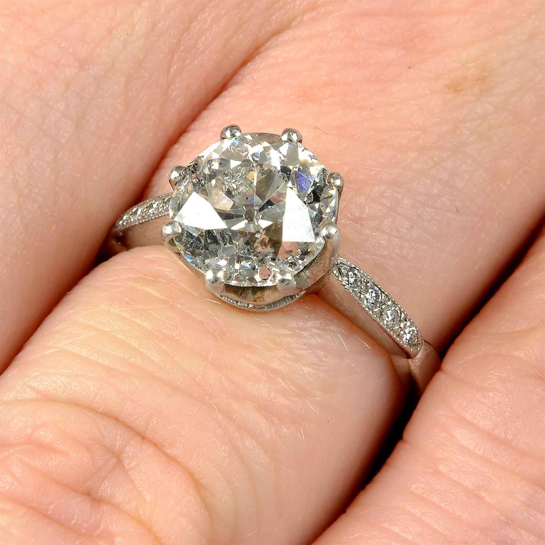 A platinum old-cut diamond single-stone ring, with brilliant-cut diamond line shoulders.
