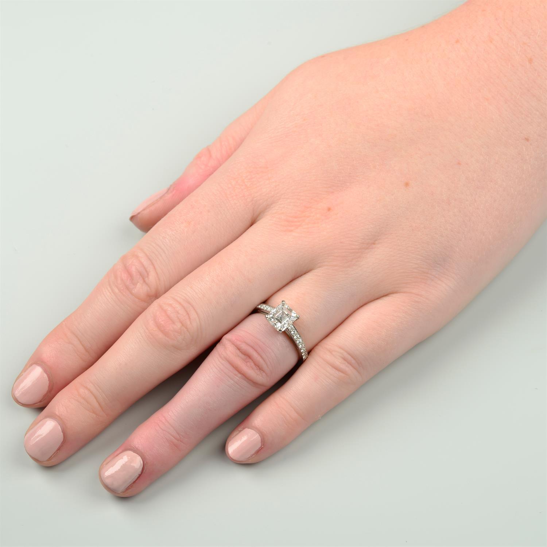 A platinum rectangular-shape diamond single-stone ring, with brilliant-cut diamond line shoulders. - Image 8 of 8