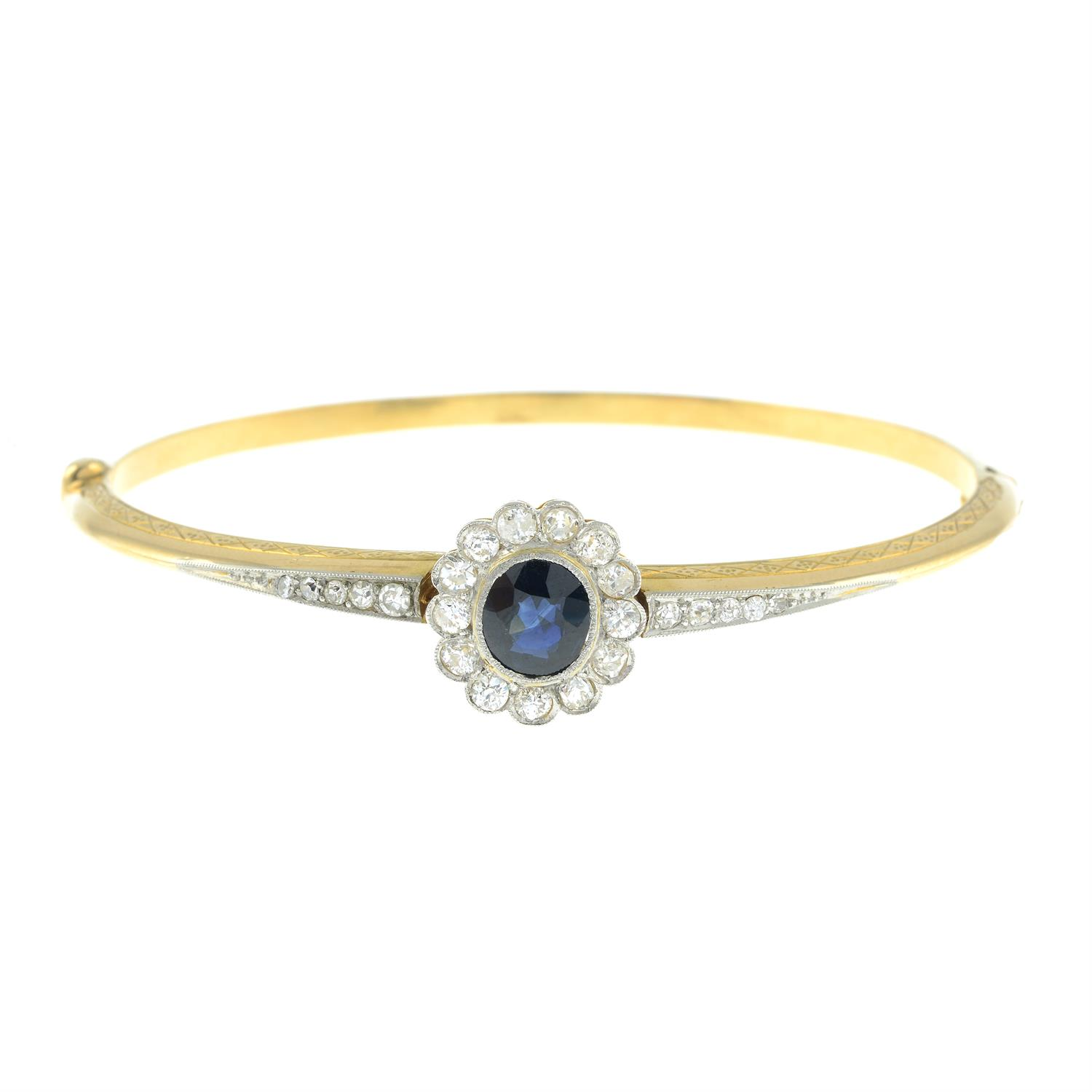 An early 20th century platinum and 18ct gold, sapphire and diamond cluster hinged bangle. - Image 2 of 3