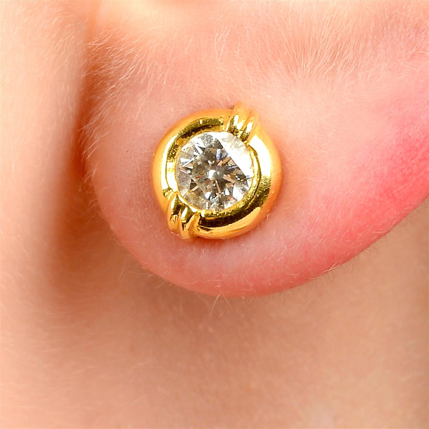 A pair of brilliant-cut diamond collet stud earrings, with raised double bar detail.
