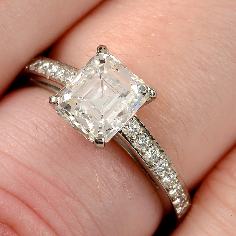 A platinum rectangular-shape diamond single-stone ring, with brilliant-cut diamond line shoulders.