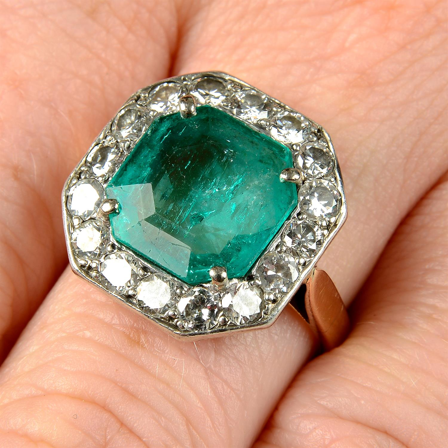 A mid 20th century silver and gold, emerald and brilliant-cut diamond ring.