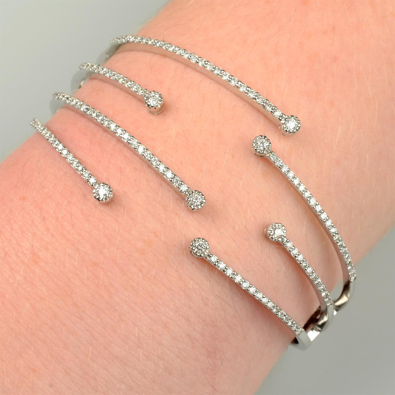 A brilliant-cut diamond open hinged bangle.