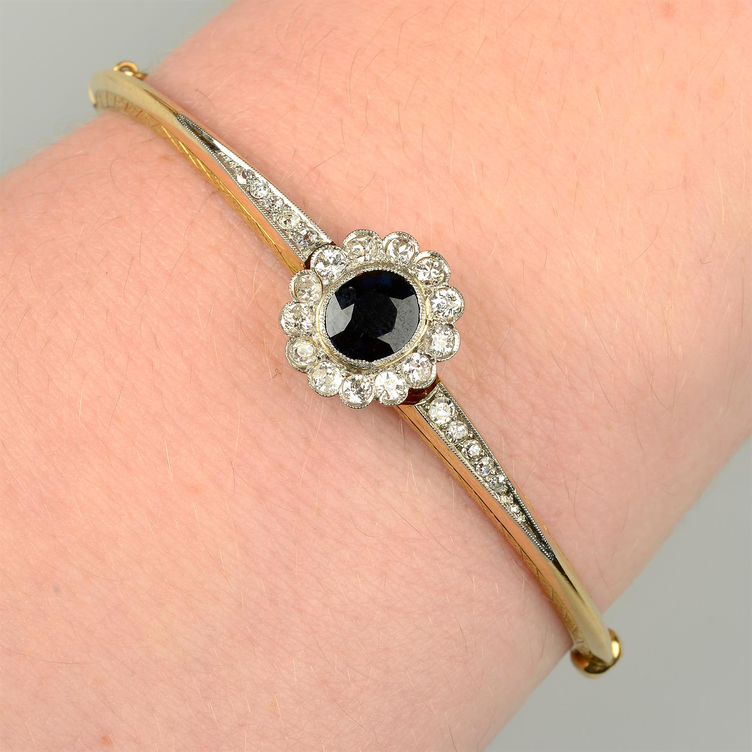 An early 20th century platinum and 18ct gold, sapphire and diamond cluster hinged bangle.