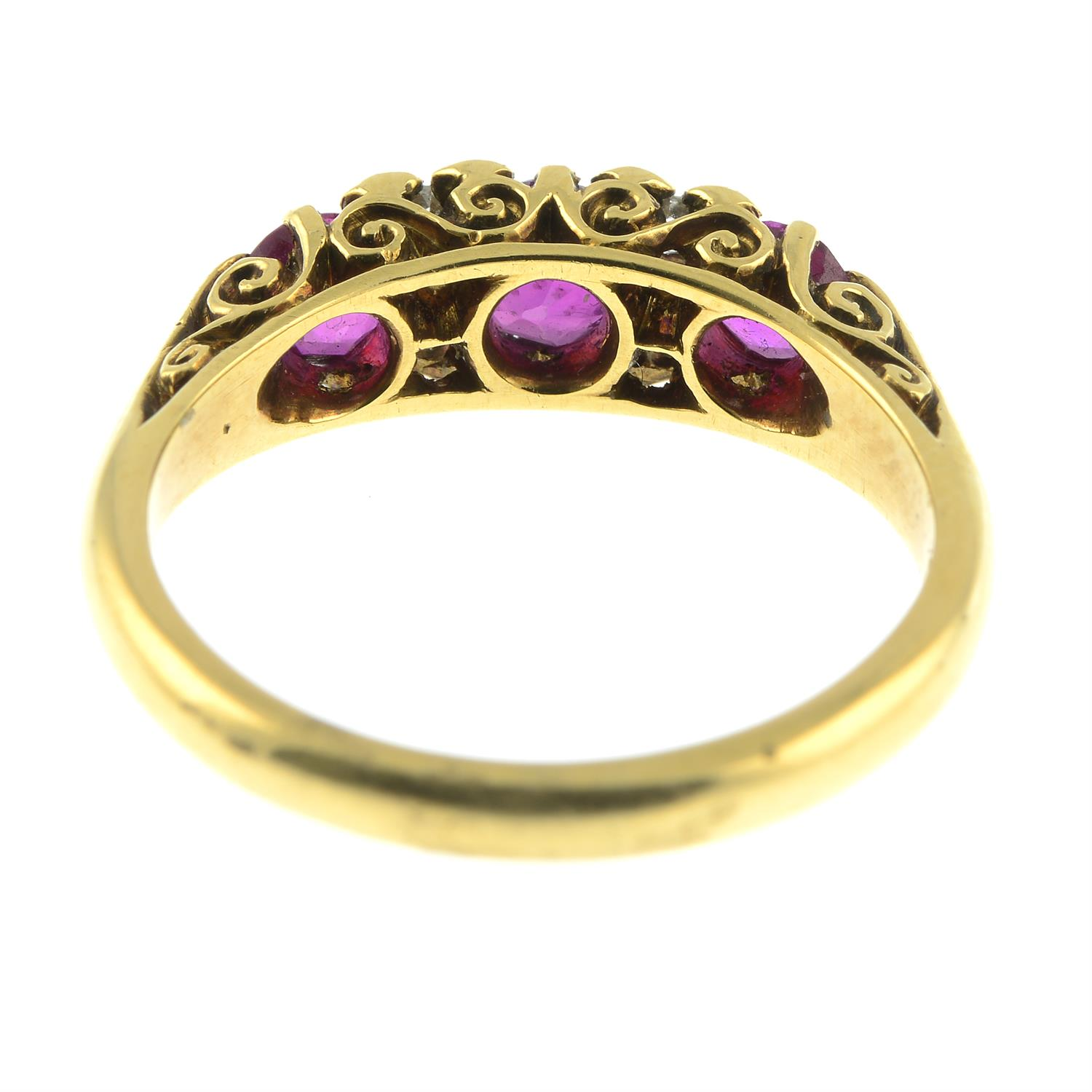 An 18ct gold slightly graduated ruby three-stone ring, with diamond double spacers and scrolling - Image 4 of 6