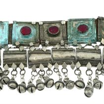 A Rashaida tribal belt with leather strap, red glass and suspended bells detail. AF.