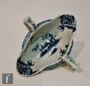 A late 18th Century Worcester twin handled sauce boat decorated with a blue and white hand painted