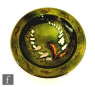 A late 19th Century shallow bowl decorated with tubelined foxgloves and foliage against a green