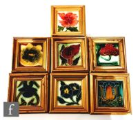Seven assorted framed 3in Art Nouveau dust pressed tiles, each with a stylised flower head to