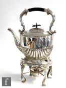 A hallmarked silver spirit kettle raised on four paw feet stand encompassing burner, all below