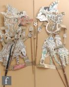 Two Indonesian Wayang theatre paper puppets, each of the characters mounted on sticks, approximate