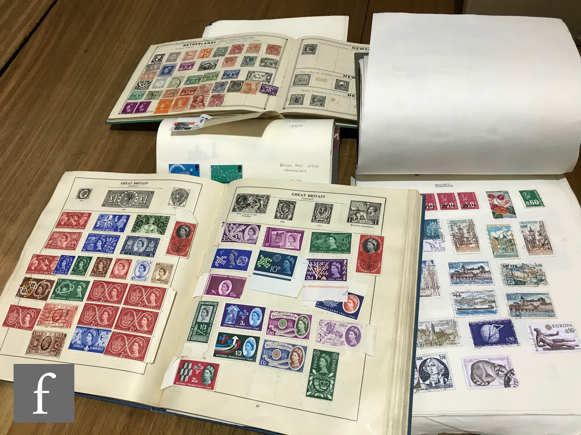 A Strand album of world and Commonwealth stamps and three other similar albums. (4)