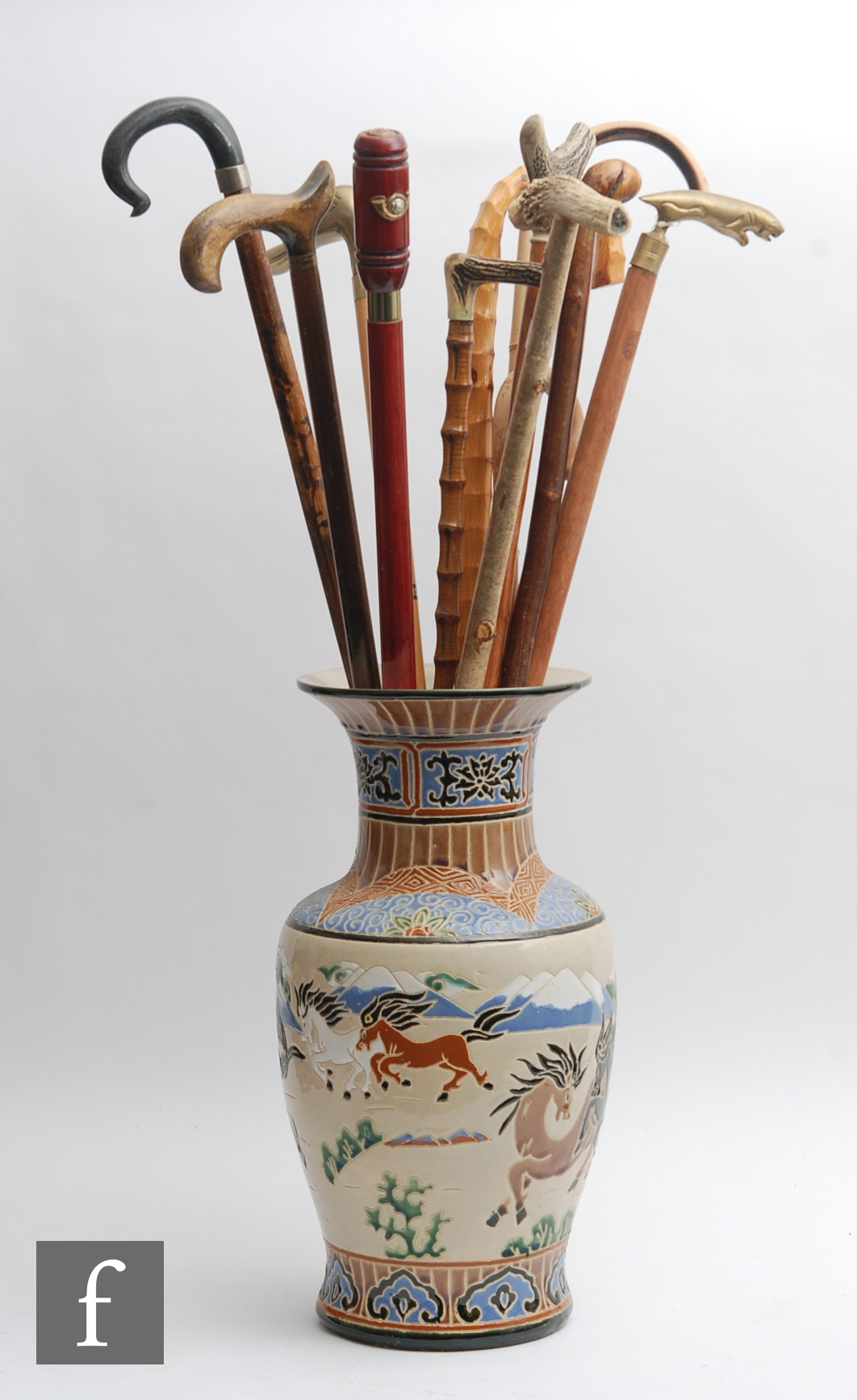 A collection of twelve walking sticks to include horn, brass and rootwood examples, all in a