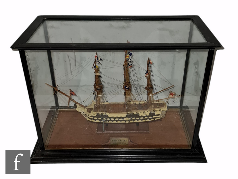 A 20th Century scale wooden model of HMS Victory, length 48cm, in ebonised display case 44cm x 58cm.