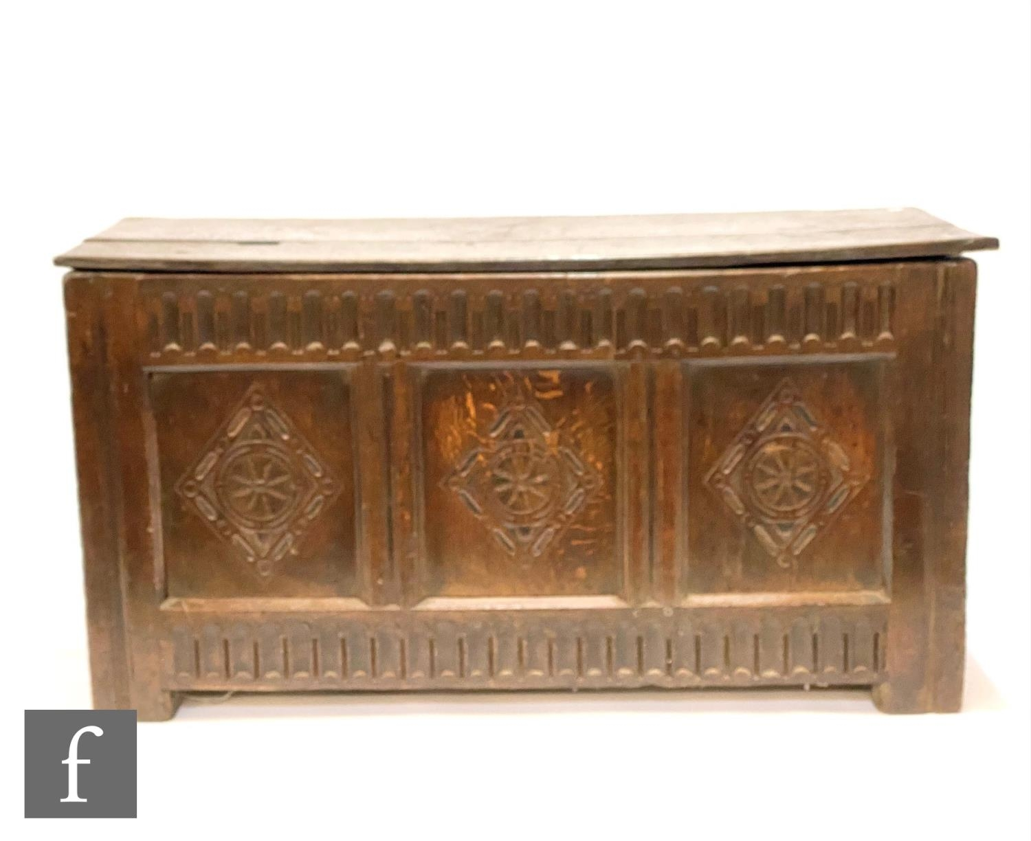 An early 18th Century carved oak coffer, the twin plank top over a lunette frieze and triple diamond