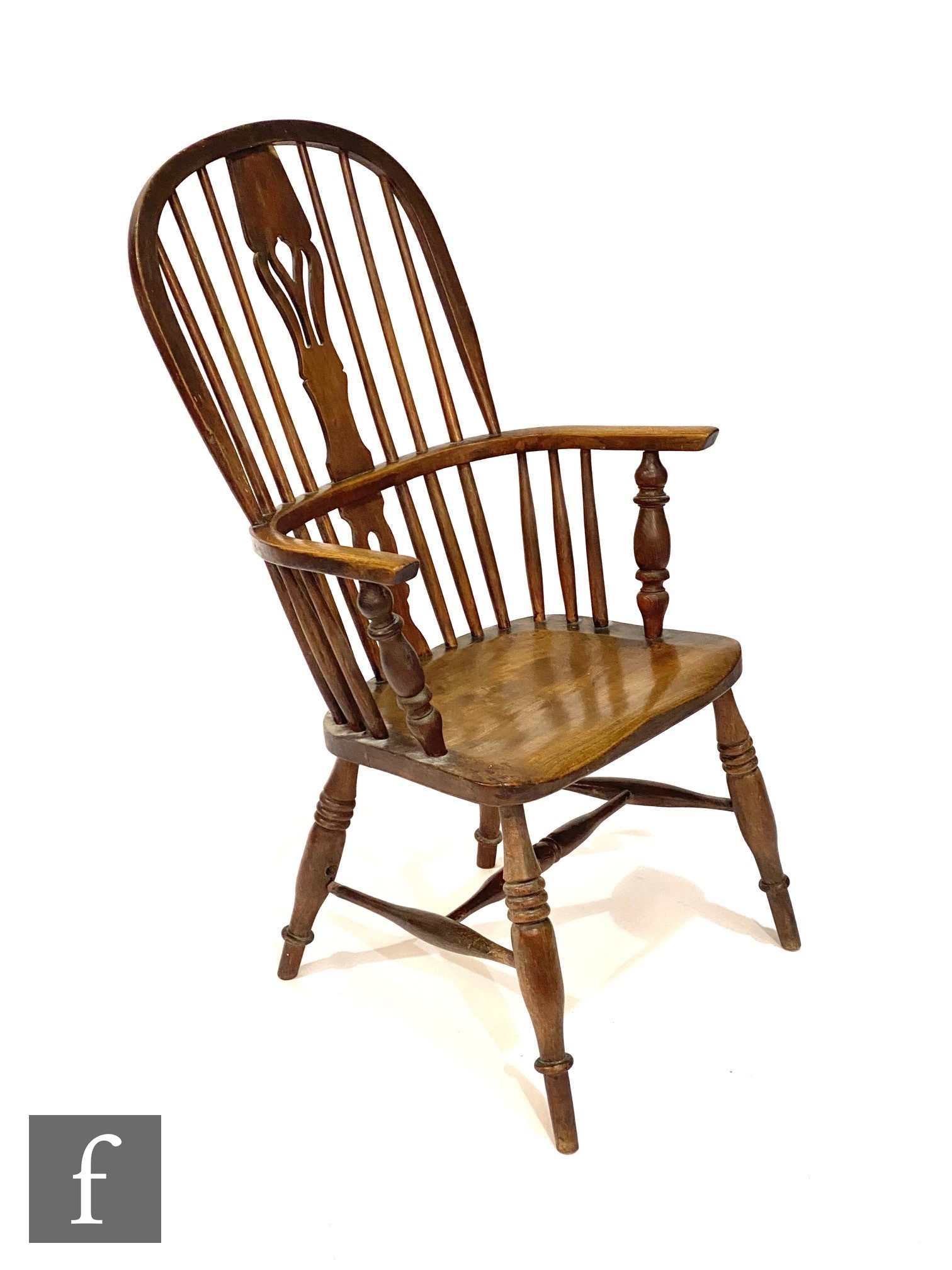 An early 20th Century ash and elm seat stick back Windsor elbow chair, on turned splayed legs united