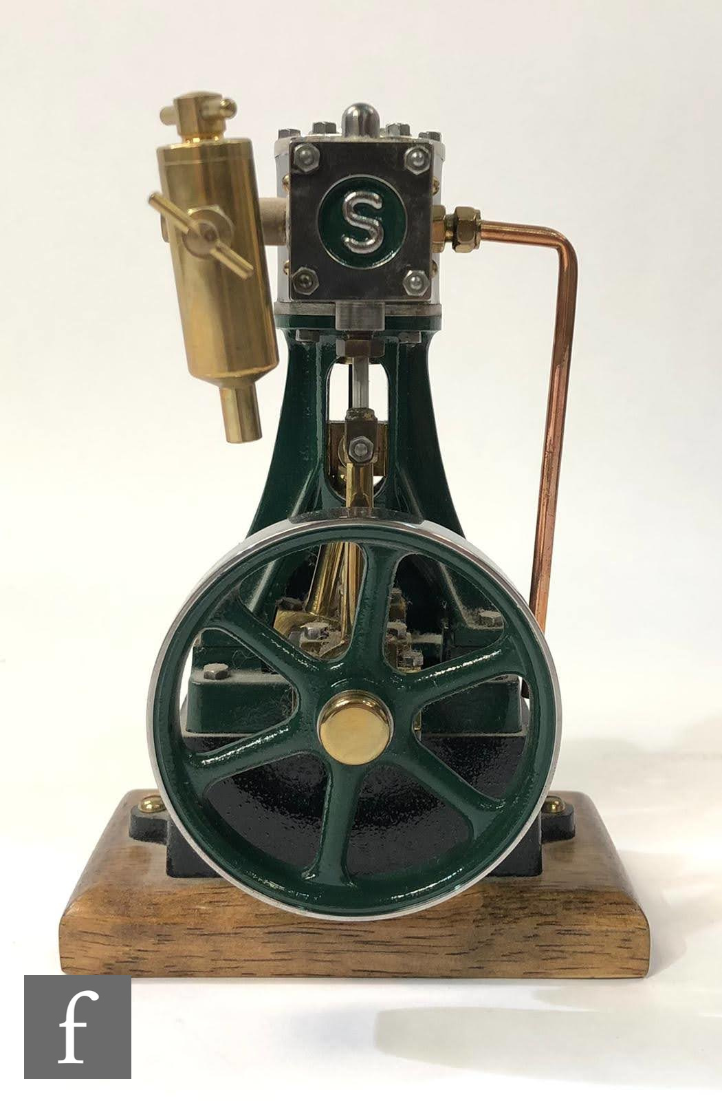 A Stuart single cylinder vertical live steam engine, painted green, with a six spoked flywheel,