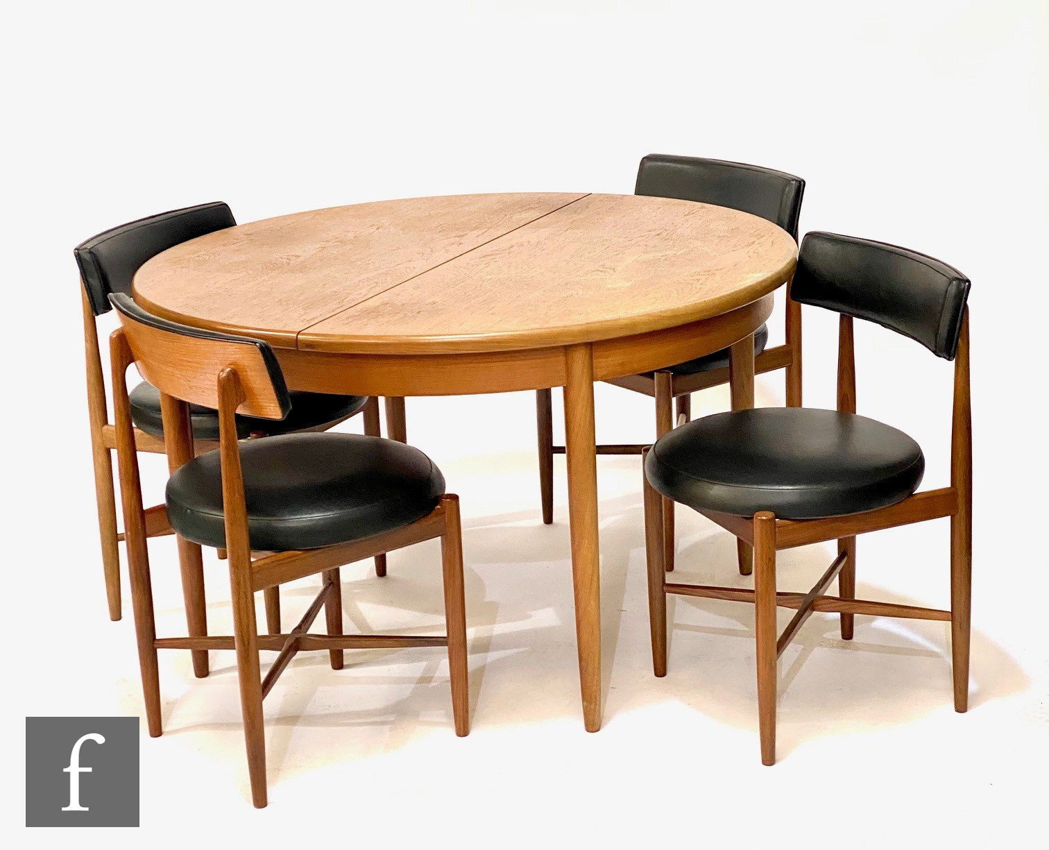 A G-Plan circular teak dining table, diameter 123cm, and a set of four black vinyl upholstered