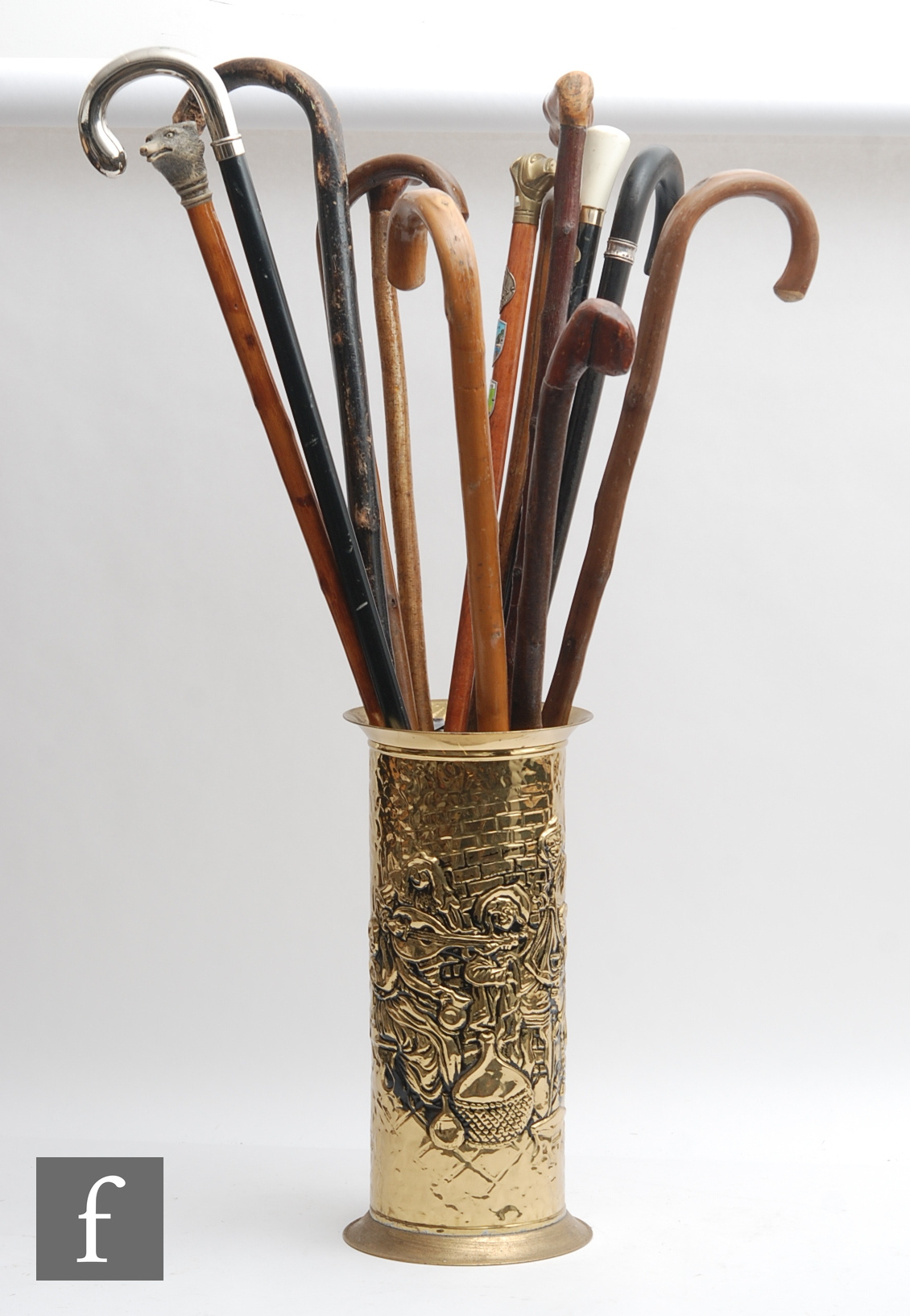 A collection of thirteen walking sticks to include animal, rootwood, brass examples, all housed in a