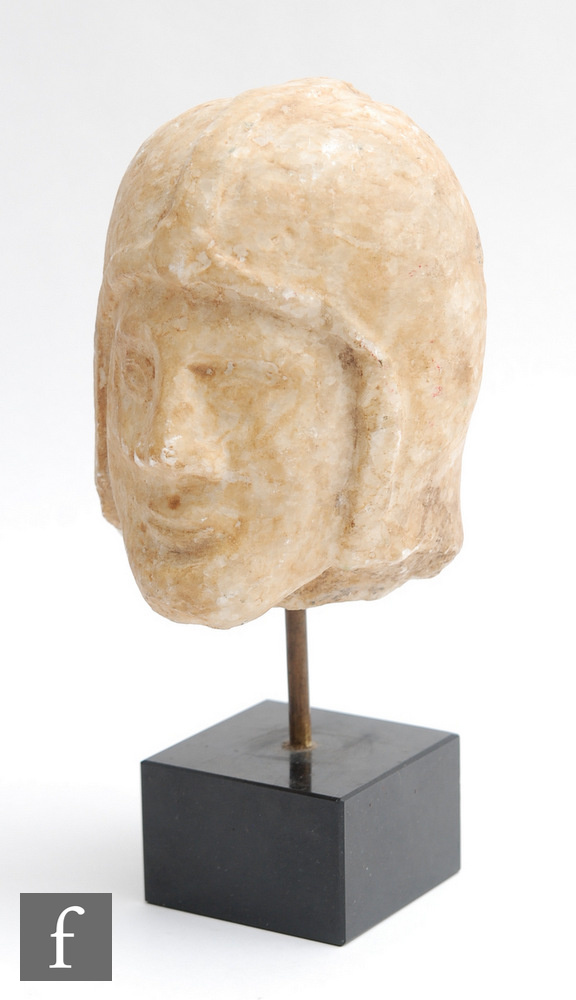 A carved marble Greek or Roman head of a soldier in Chalcidian type helmet with pronounced facial