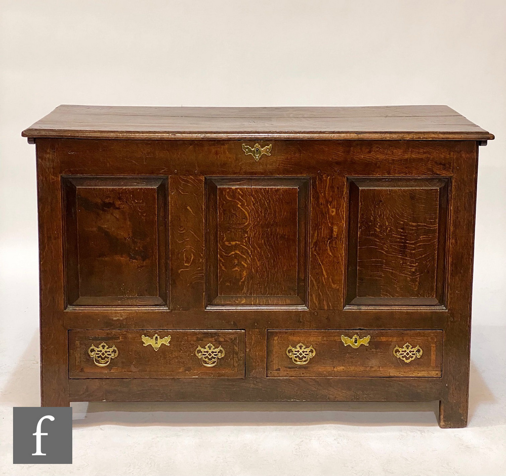 A 18th Century oak mule chest, the moulded edge plank top over fielded triple front above two