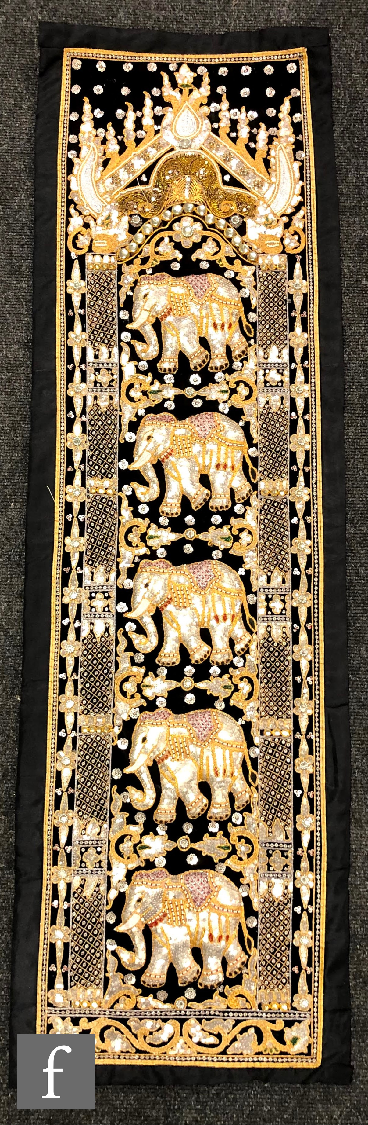 A South East Asian wall hanging on black cloth embroidered with sequins and gilt thread, depicting