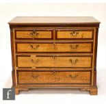 A George III oak and mahogany crossbanded chest of two short and three long drawers, brass drop