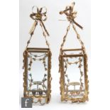 A pair of gilt metal and glass hanging lanterns, the four glass square section shades, applied