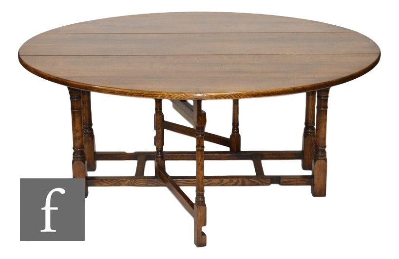 A 20th Century large oak circular gate-leg dining table, raised to a stretcher frame, 183cm in