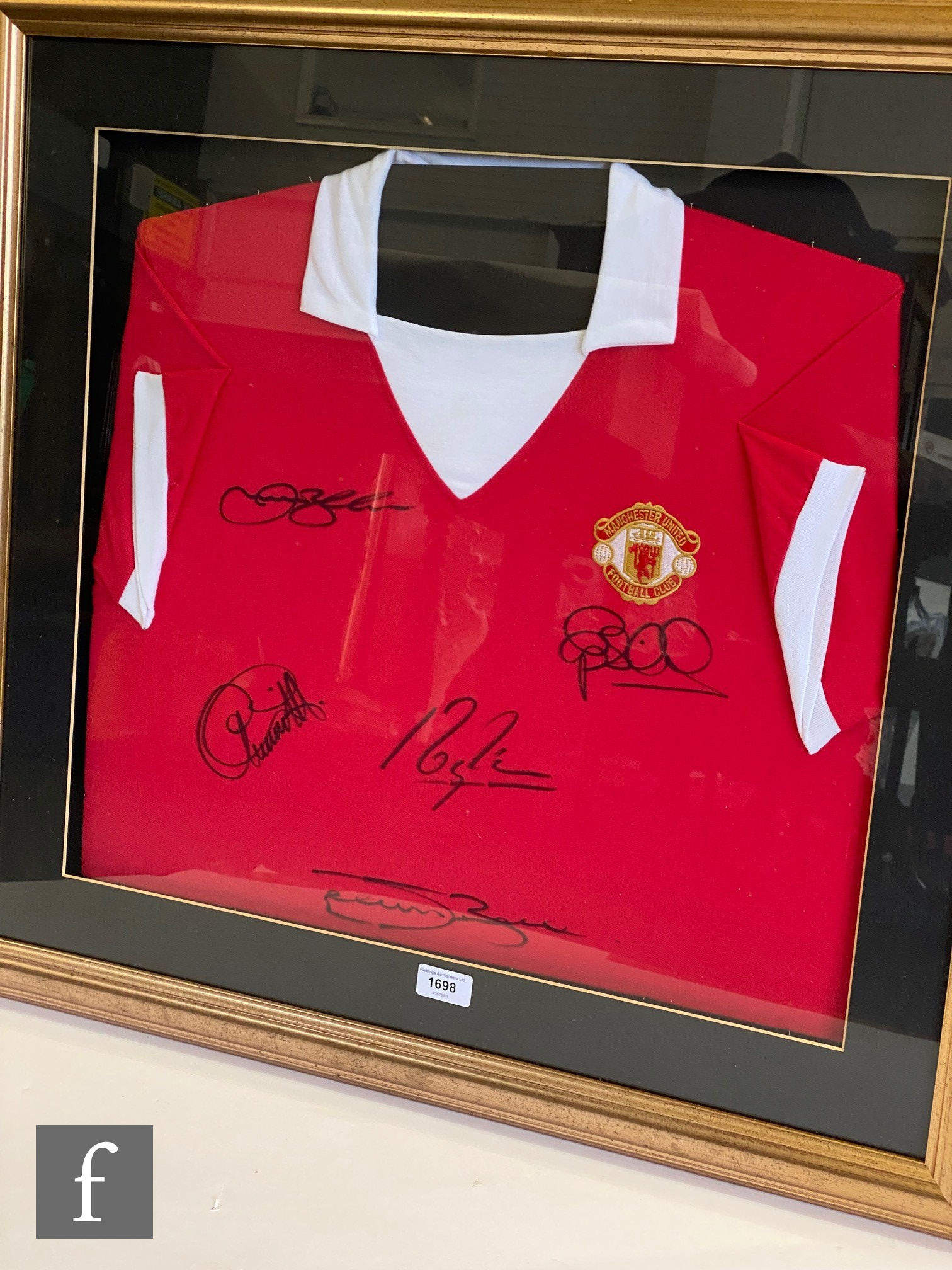A Manchester United red and white shirt signed by five captains, Steve Bruce, Eric Cantona, Peter