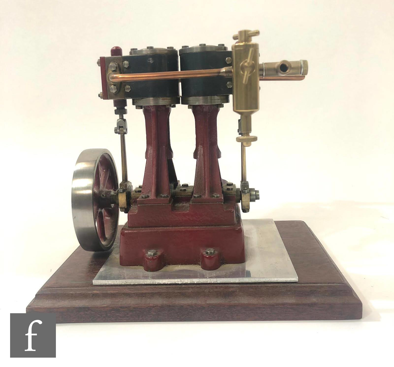 A vertical twin cylinder marine engine, painted in maroon with six spoked flywheel, with detached