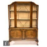 An Edwardian figured walnut display cabinet with projecting serpentine glass sides and front