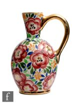 A 1930s Art Deco Boch Freres jug decorated with hand painted flowers and foliage with gilt