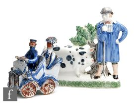 A later 20th Century Rye Pottery model of a farmer stood in a blue smock beside his Sussex pig,