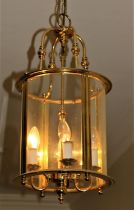 A Georgian style brass Hall Lantern, with domed glass and shaped supports, 2' high (61cms). (1)
