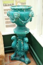 A pair of very large turquoise coloured glazed porcelainmatching Urns and Stands, the urns with