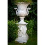A large heavy set of 4 unusual cast iron Garden Urns, each relief cast with vases of flowers and two