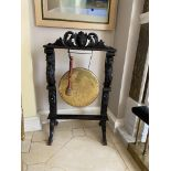 A 17th Century style carved and ebonised Hall Gong, with lion mask crest on two double scroll