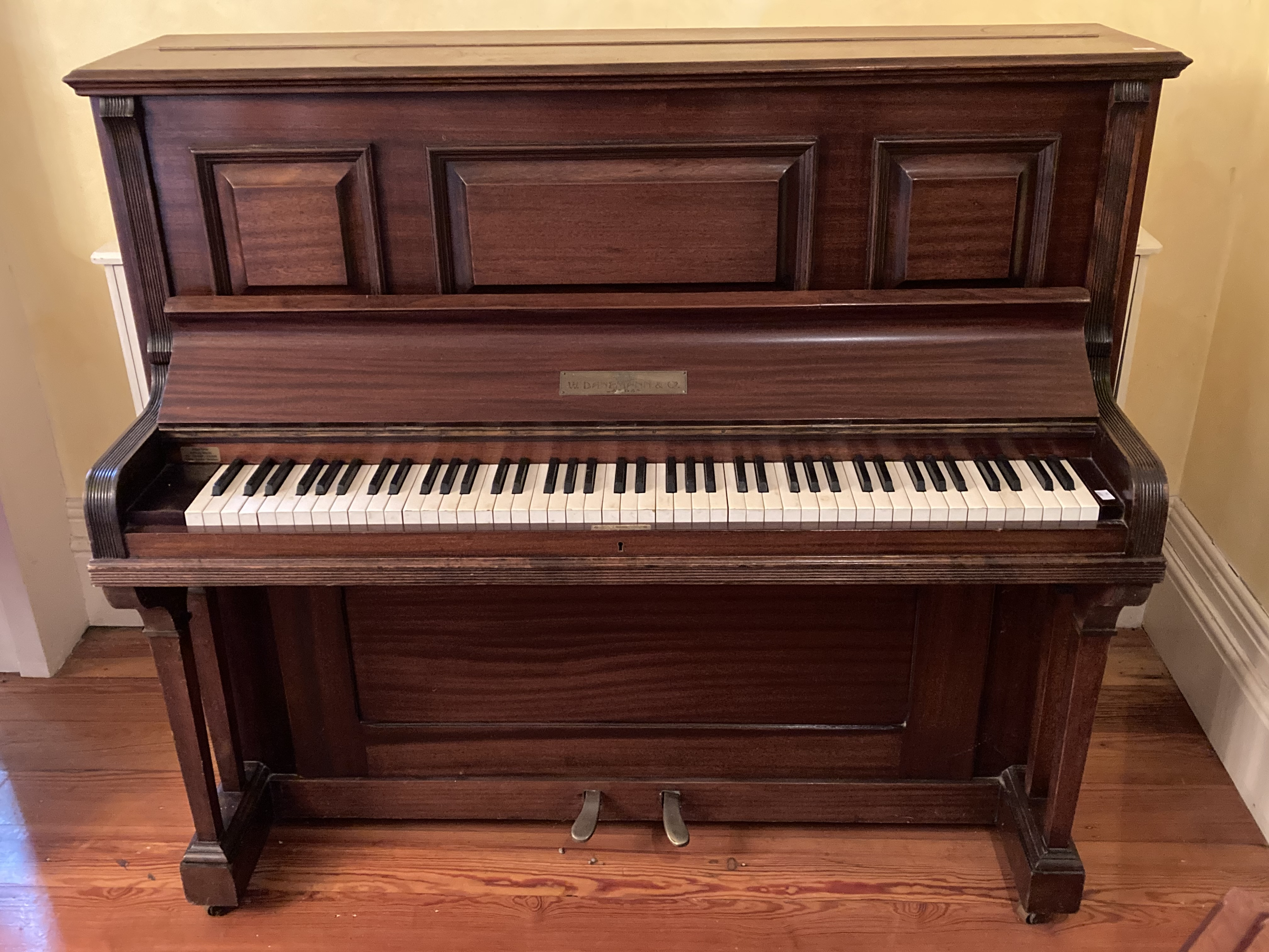 A good upright iron frame Piano, by W. Danemann & Co., London in mahogany case, 54 1/2'' (