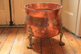 A brass mounted copper Planter or Fuel Bin, with lion paw feet, 14 1/2'' x 15'' (37cms x 38cms). (1)