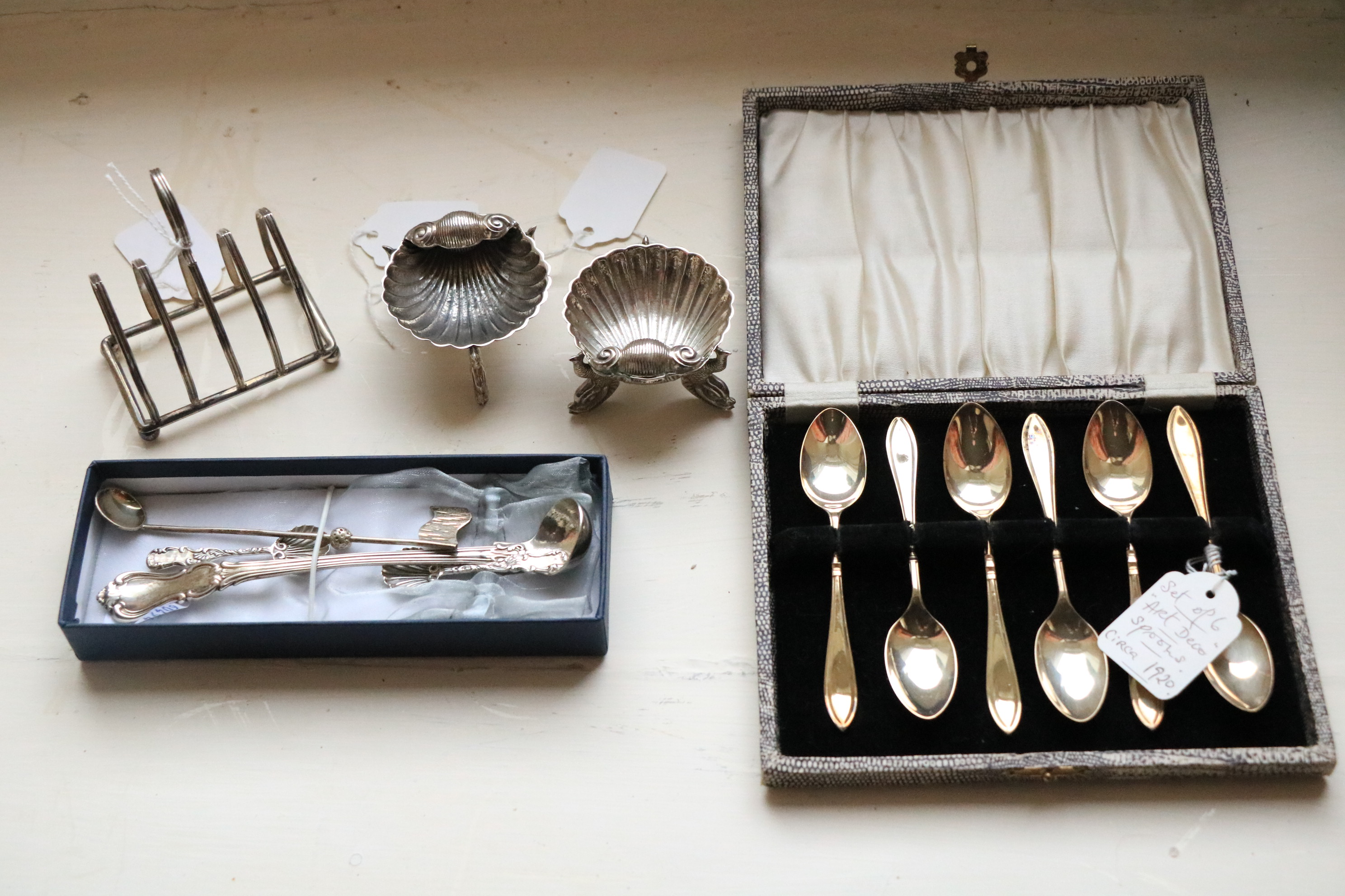 An unusual pair of Sterling silver Shell shaped Salts, each on tri-dolphin legs with two shell