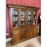 A Victorian style mahogany Library Bookcase, with moulded pediment above four arched and glazed