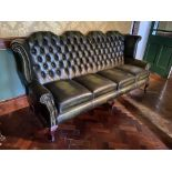 A button back four seater Wing Back Settee, covered in dark hide with four cushion seat on