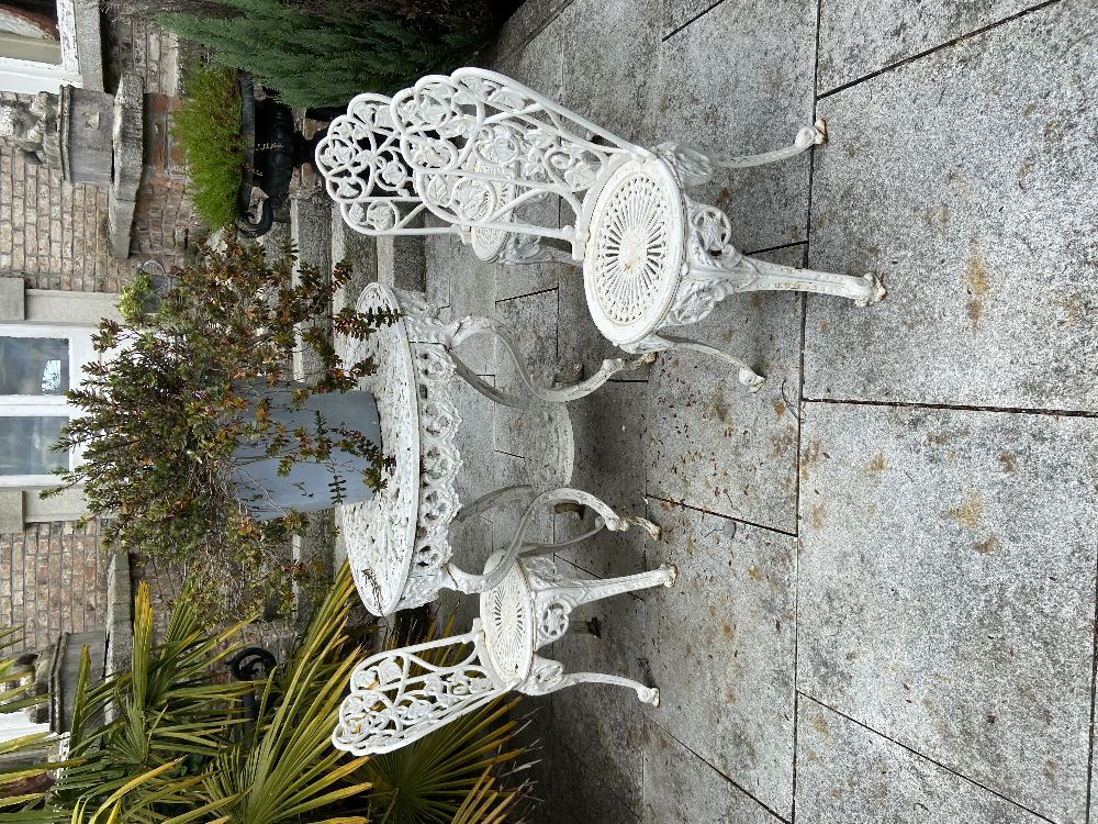A four piece cast metal Patio Set, comprising a heavy circular table with open work top on four