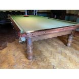 A full size Billiard / Snooker Table, in mahogany and covered in green baize raised on 8 heavy